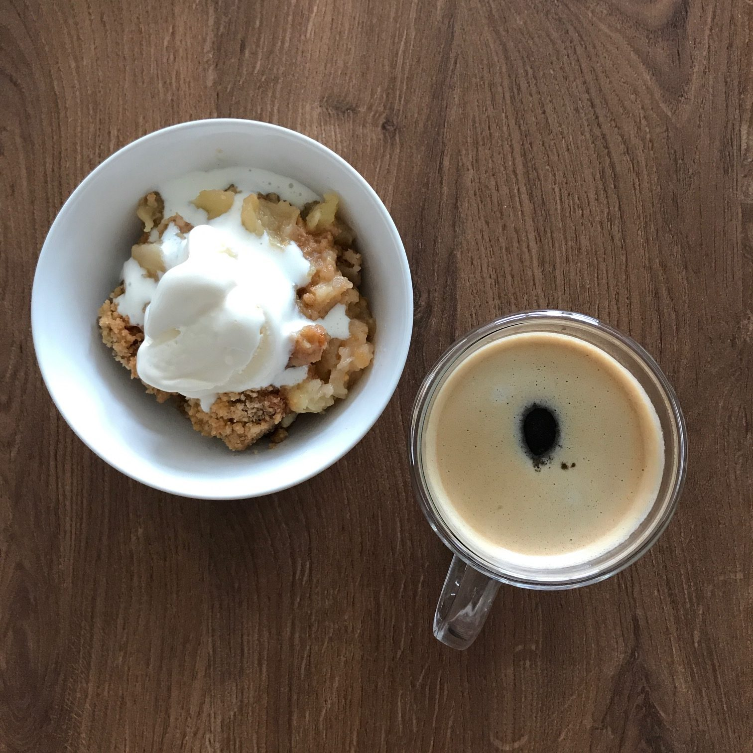 szarlotka z lodami w miseczce z kawą na ławie jabłka pod kruszonką